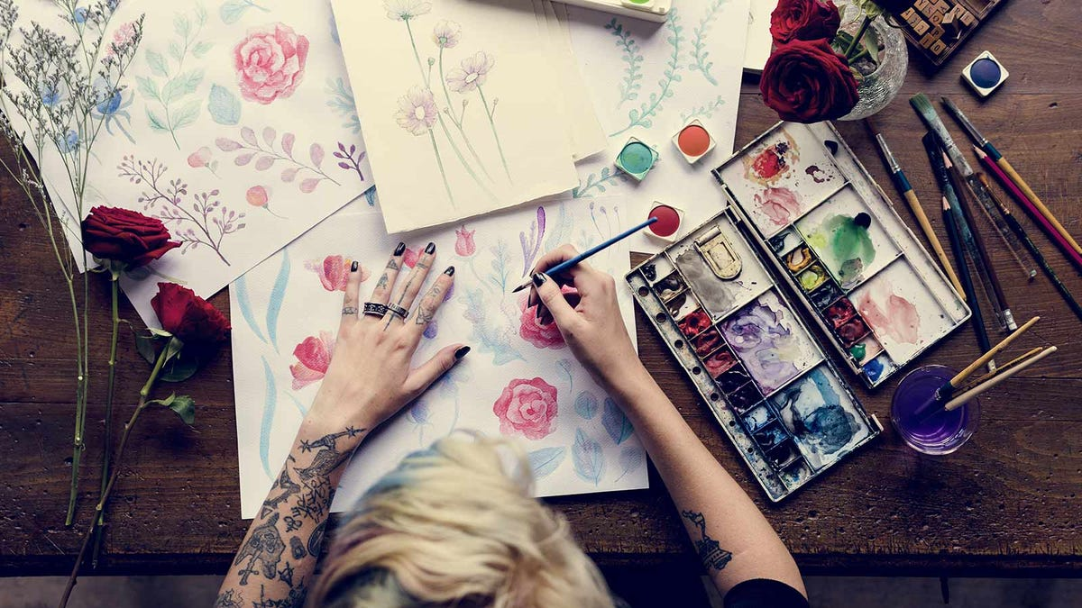 Overhead view of a woman painting roses.