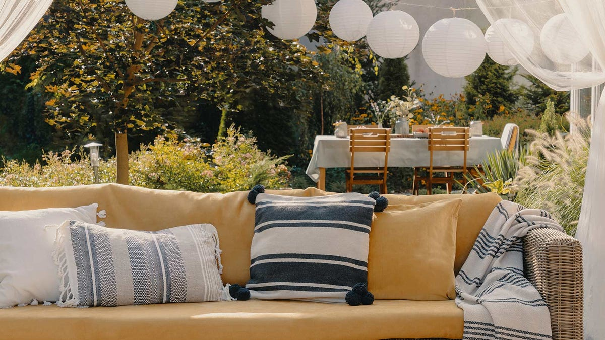 A beautiful outdoor space with paper lanterns and a couch.