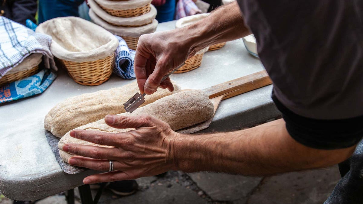 A man scouring bread with a razor lame.
