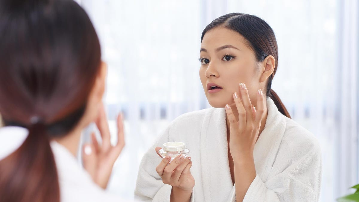 Woman applying cream to her face in front of the bathroom mirror.