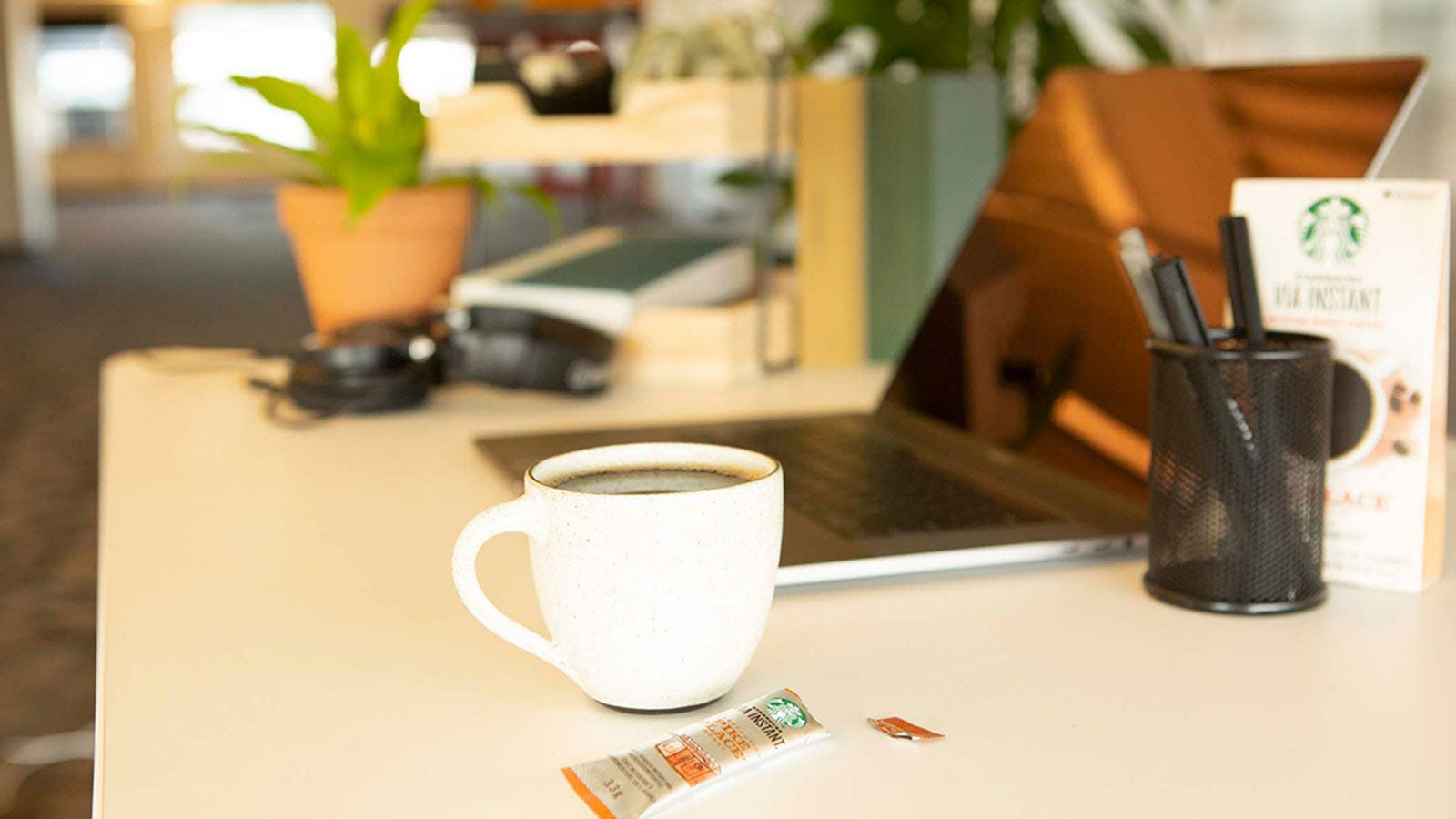 A cup of Starbucks Via instant coffee next to a laptop.