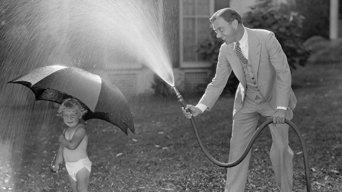 A vintage photo of a father in a suit spraying water from a hose over a toddler holding an umbrella.
