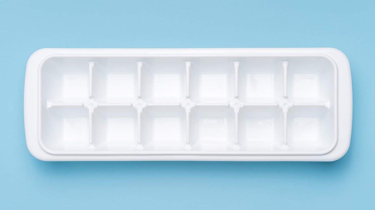 An empty ice cube tray on a blue background.