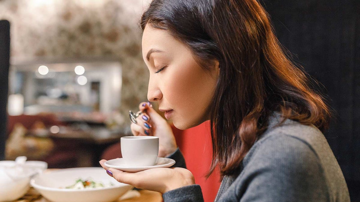 Woman smelling the aroma of a fresh cup of espresso.
