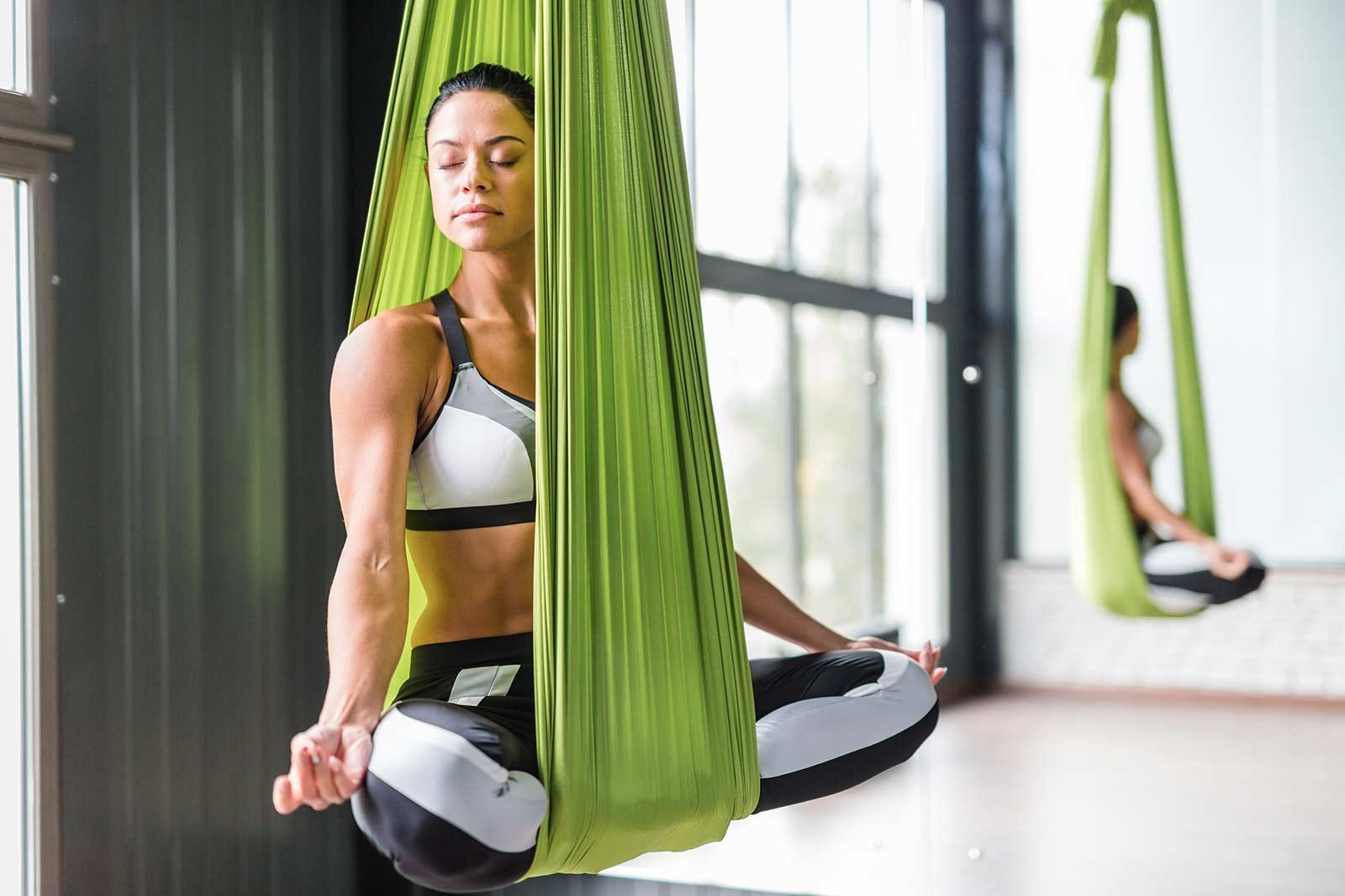 A woman meditating in a yoga swing.