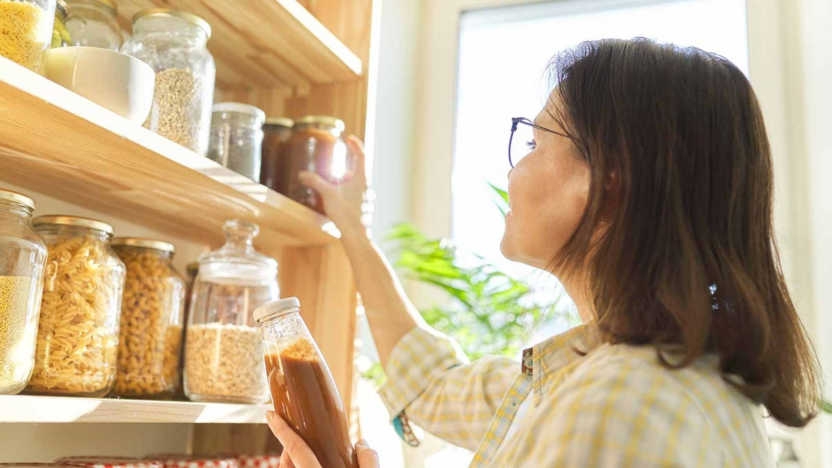 Woman organizing her pantry with repurposed pickle jars and other glass containers.