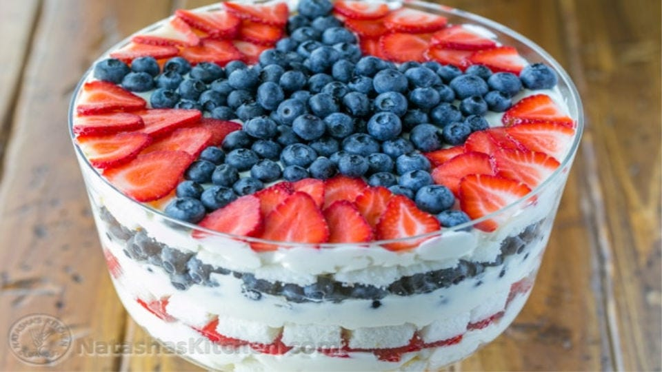 A berry trifle layered with angel food cake, fresh strawberries and blueberries, and cream cheese frosting.