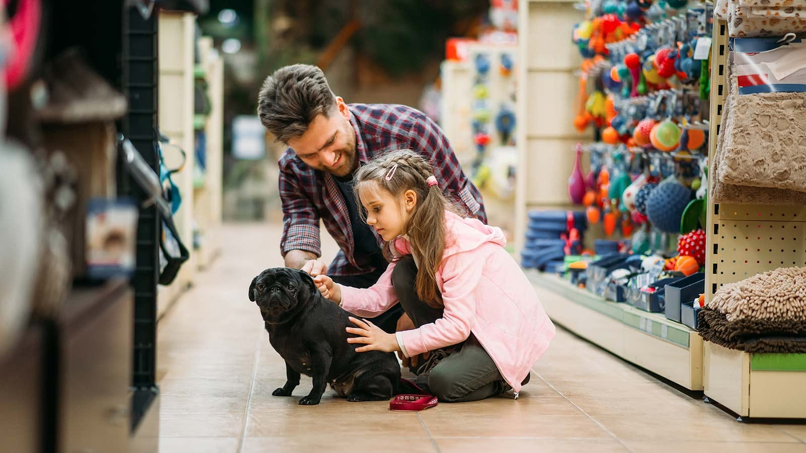 A father and daughter with their puppy at a pet store.