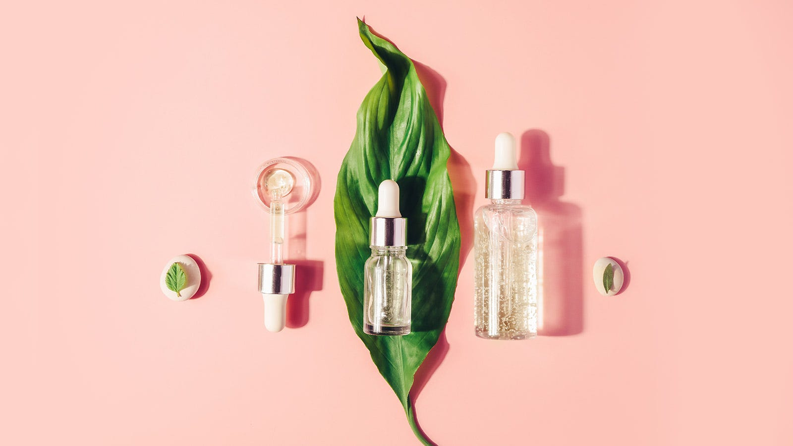 Various face serums laid out on a pink background with plant leaves.