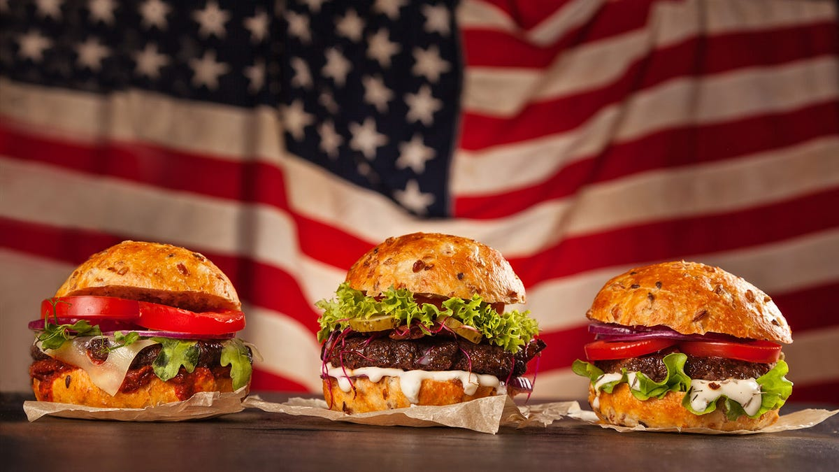Several burgers sitting in front of the American flag.