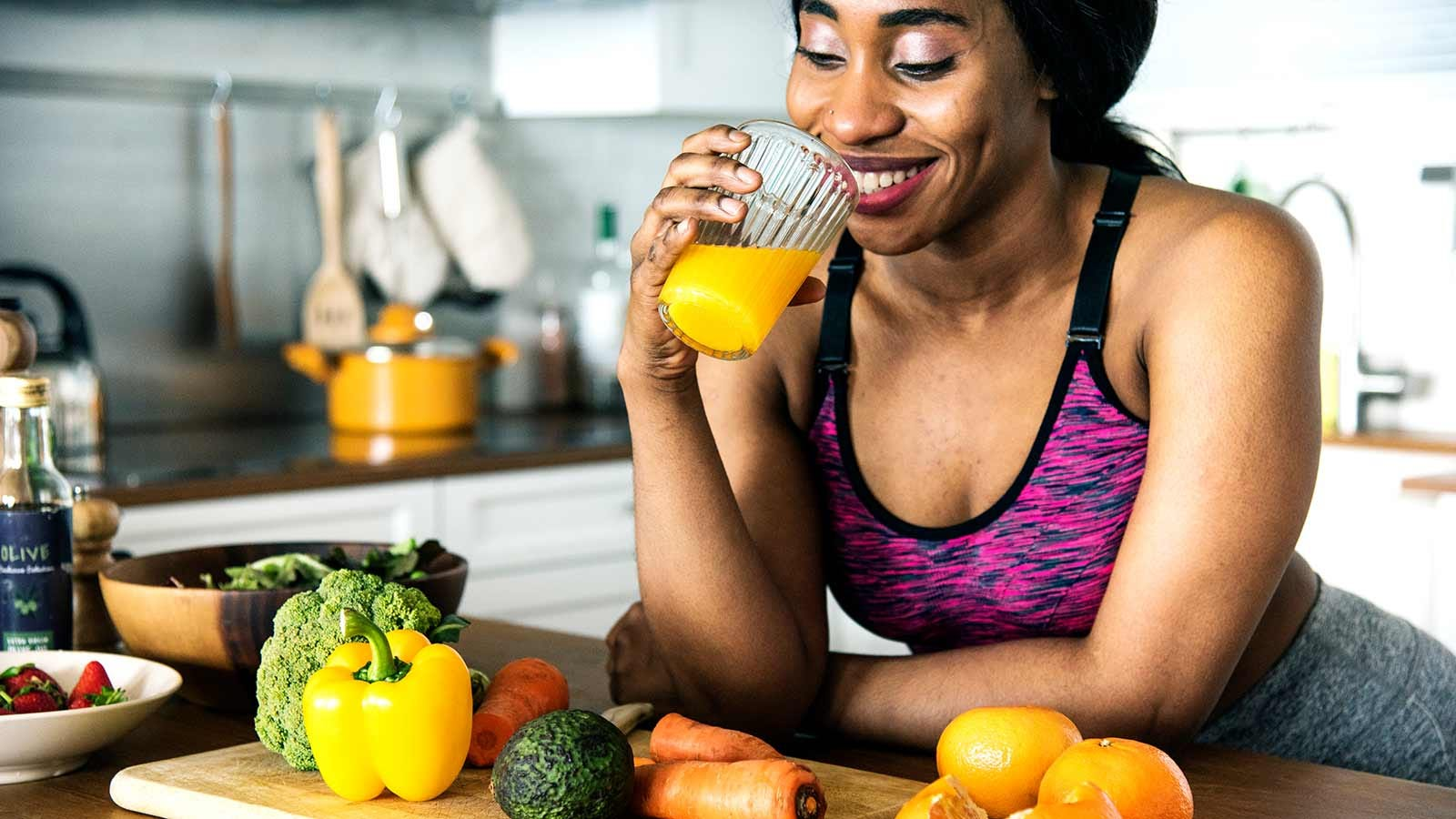 A woman drinking fresh orange juice while leaning on a counter loaded with fresh produce.