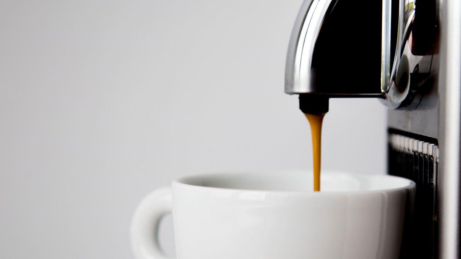 A capsule coffee machine dispensing coffee into a mug.