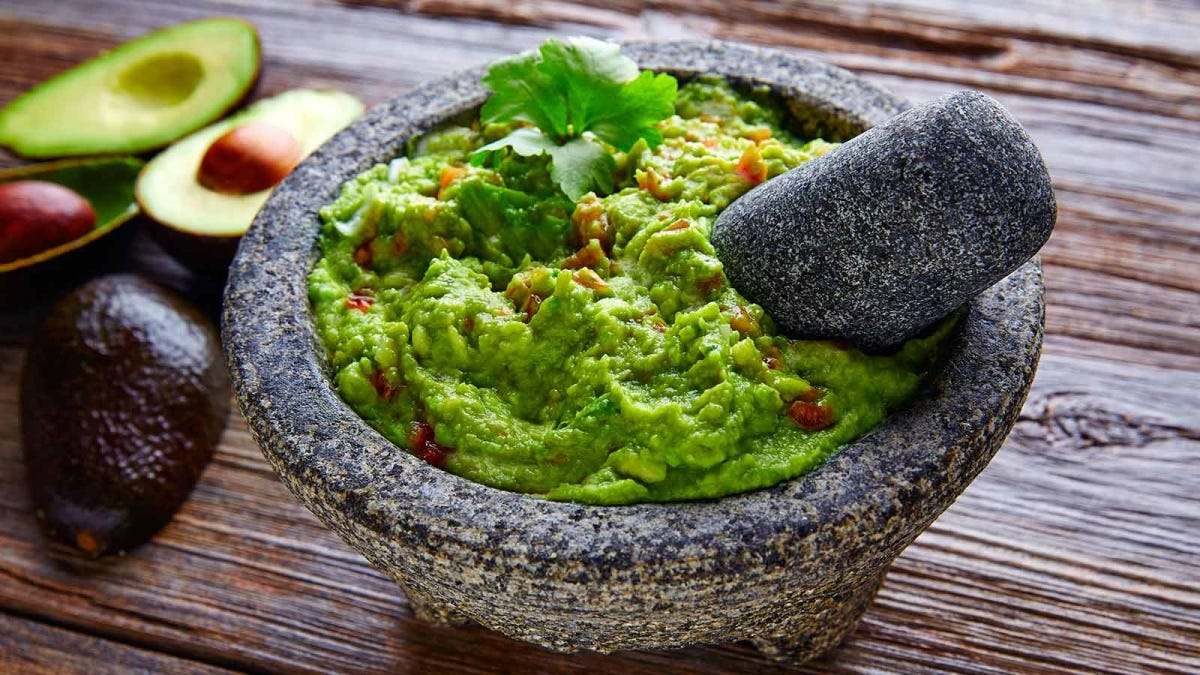 A pestle full of guacamole sits on top of a table.