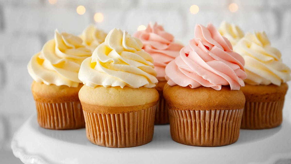 Cupcakes with light yellow and pink frosting on a cake stand.