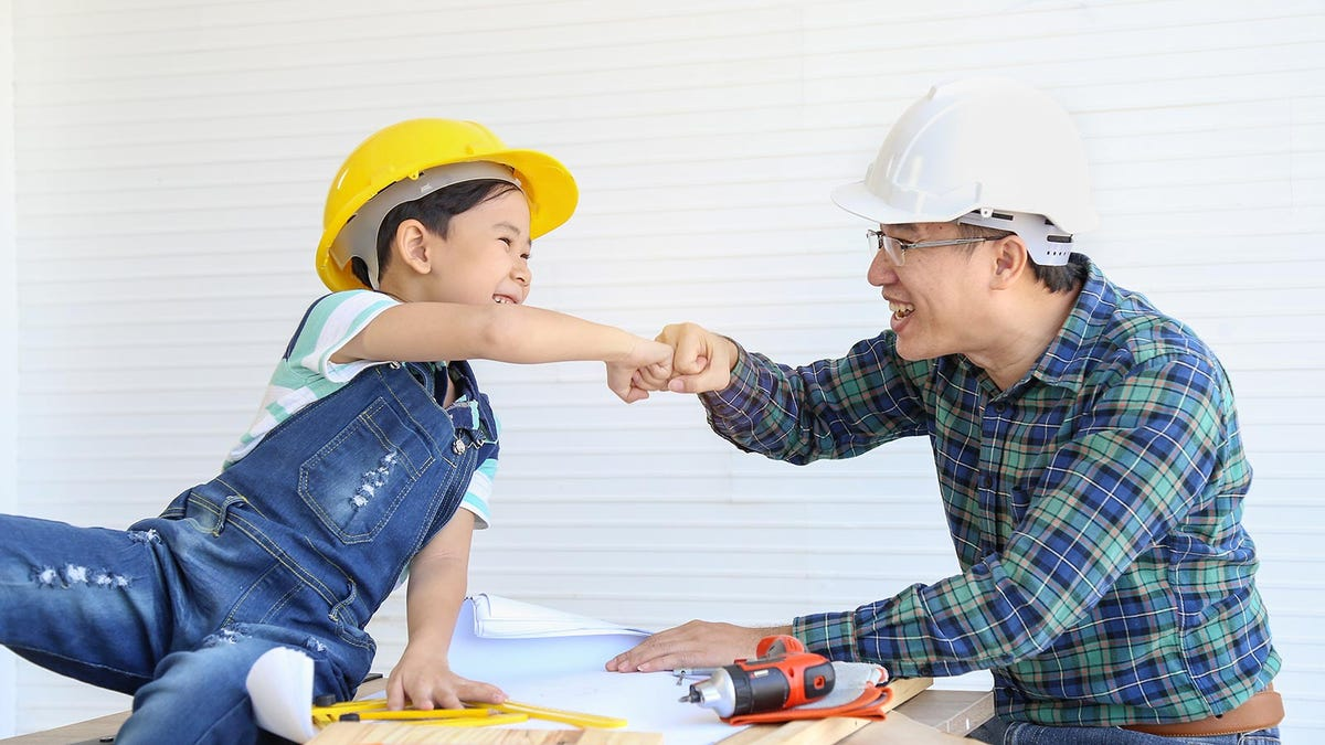 A father and son sharing a fist bump while wearing hard hats at a job site.