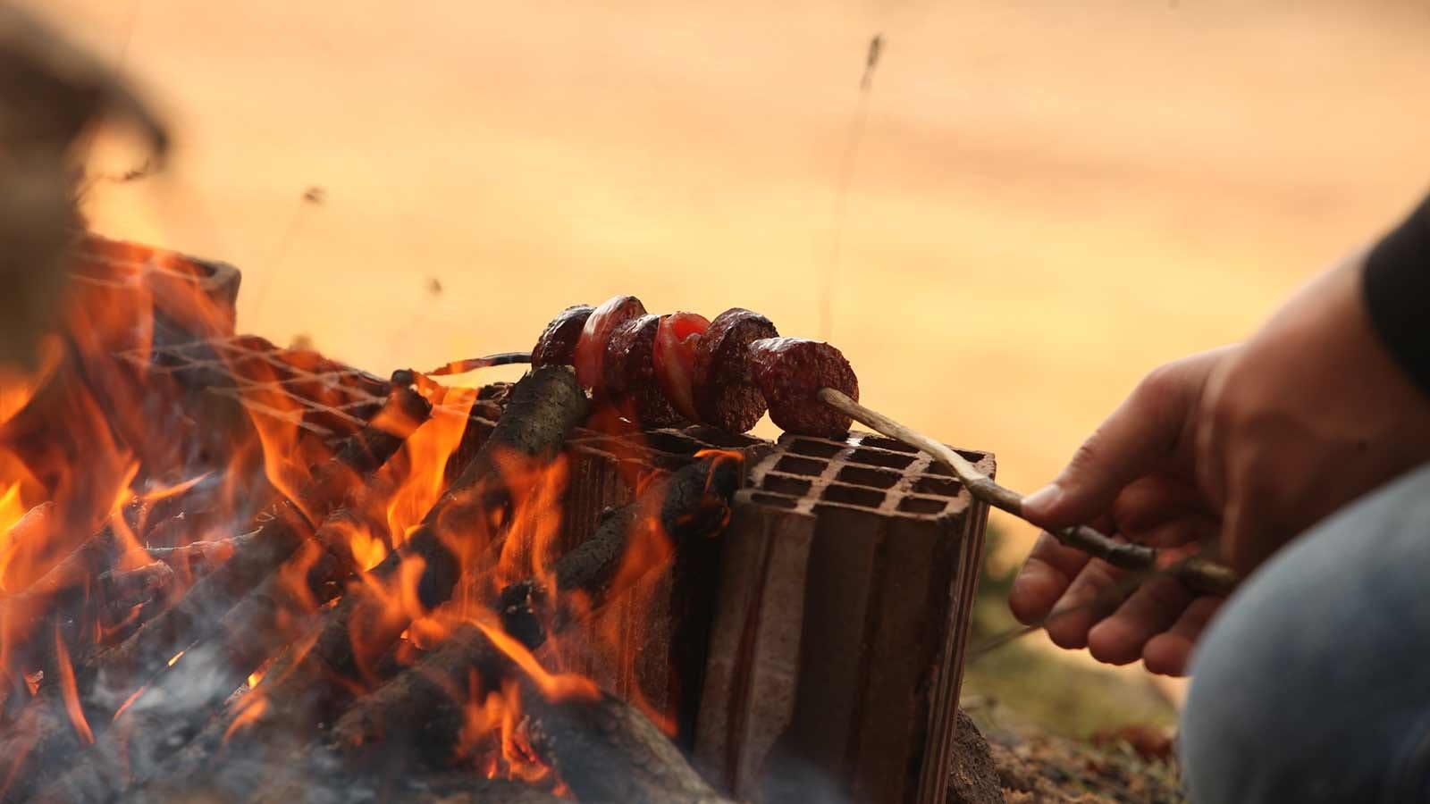Roasting veggies over an open fire on a skewer.