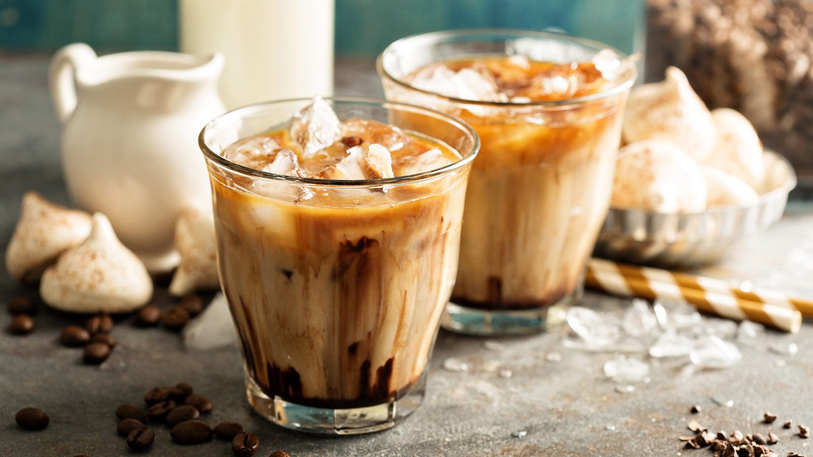 A creamy iced coffee cocktail on a table with the ingredients and meringue cookies.