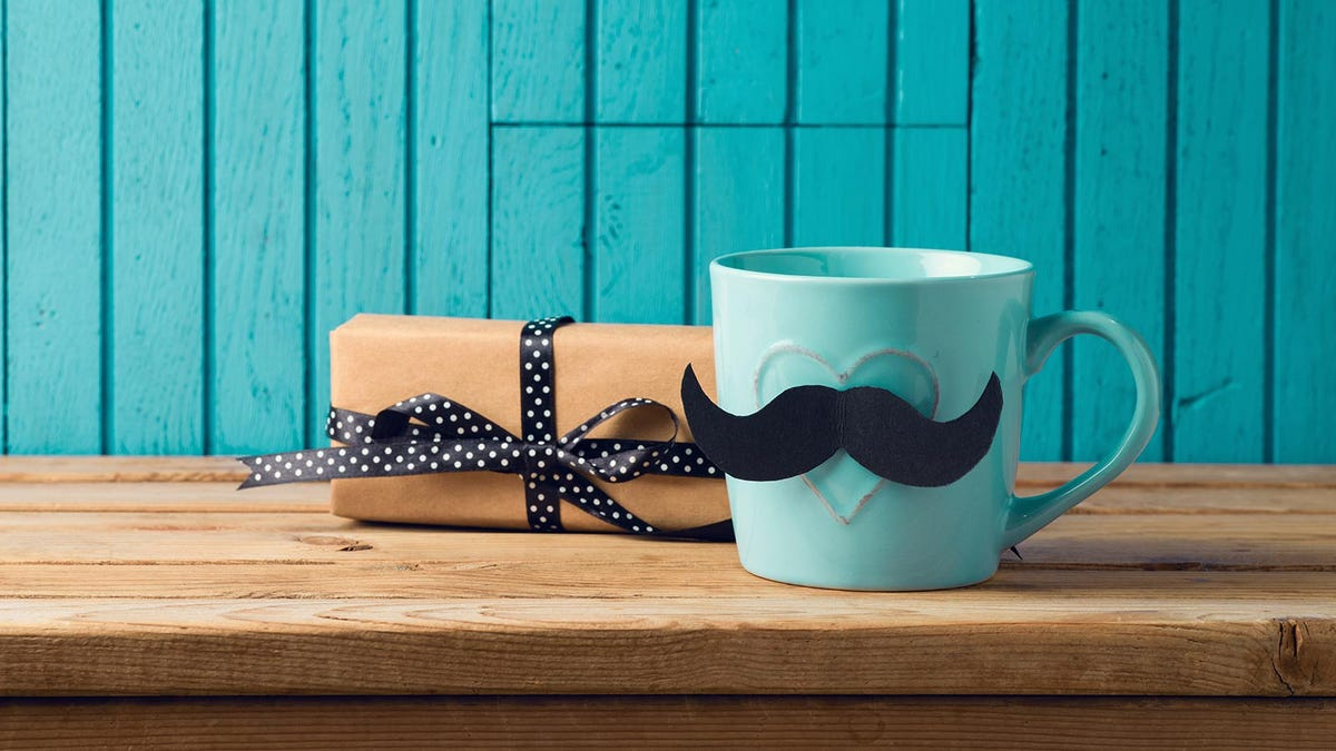 A gift box next to a mug with a paper mustache.