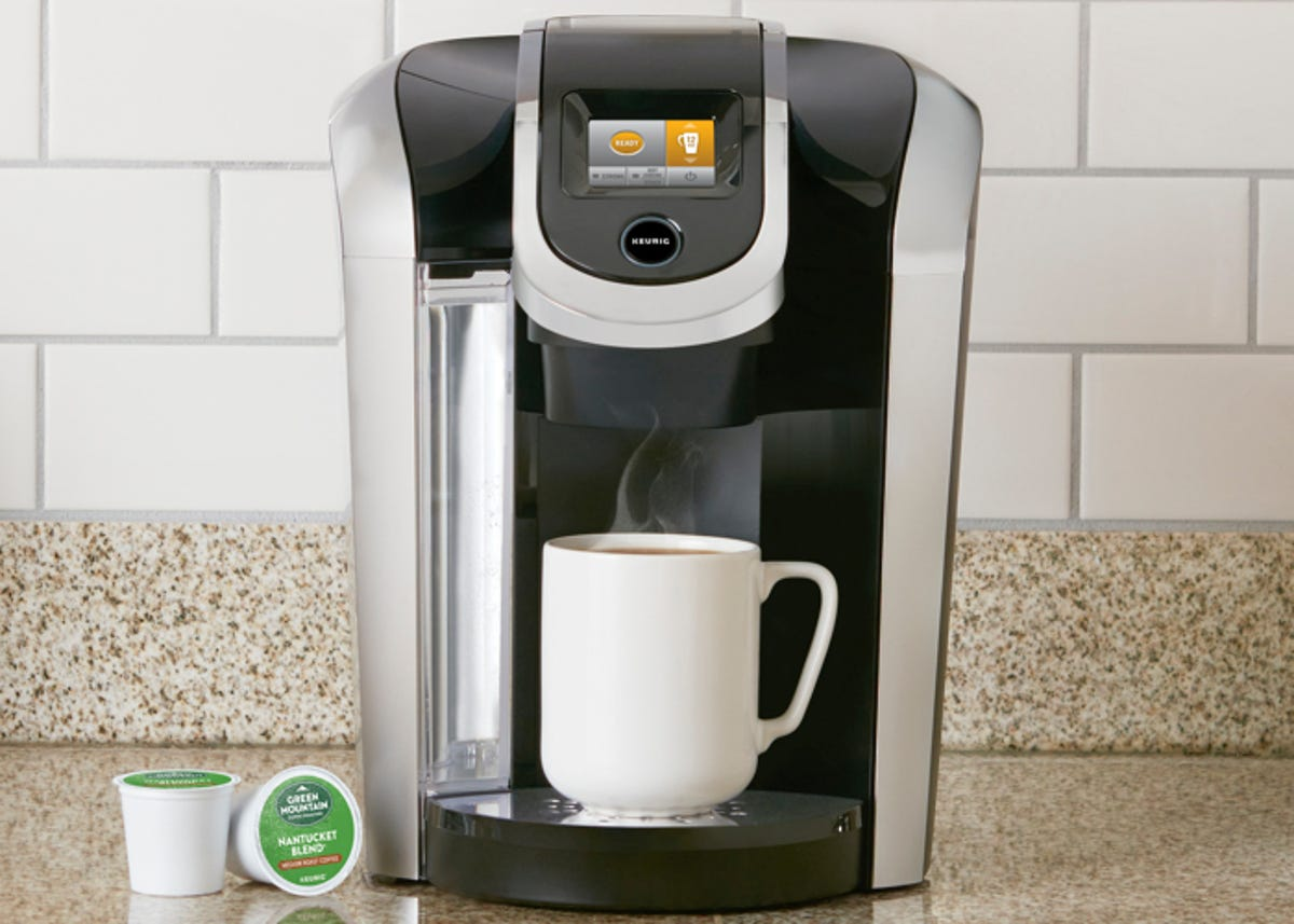 Keurig coffee maker on a countertop with a freshly filled mug of coffee