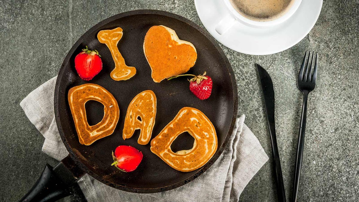 """""""I love dad"""" spelled out with pancakes in a skillet."""