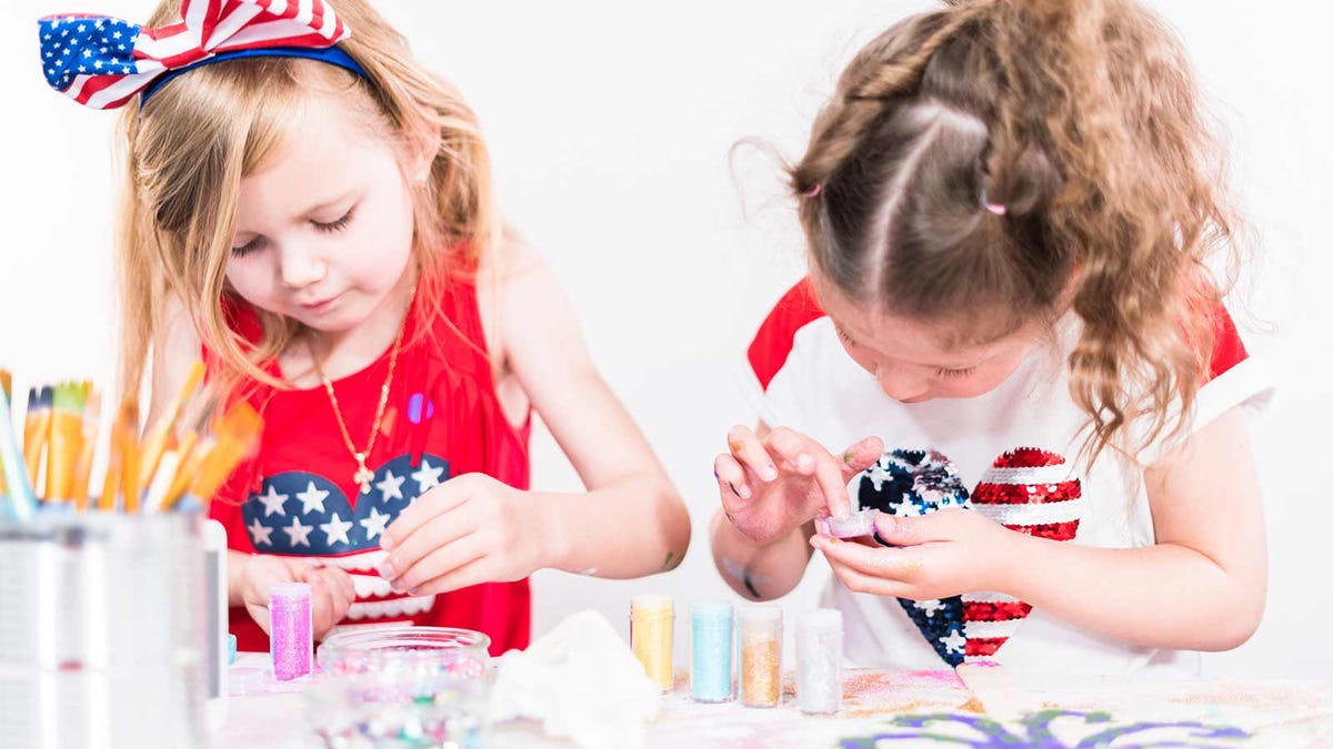 Two little girls adding glitter to their crafts.