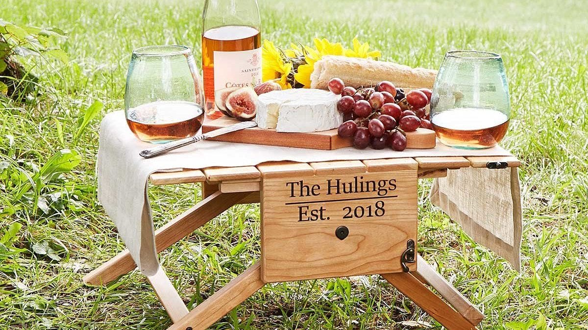 A personalized Picnic Table and Wine Carrier folded out and covered with wine, cheese, bread, and grapes.