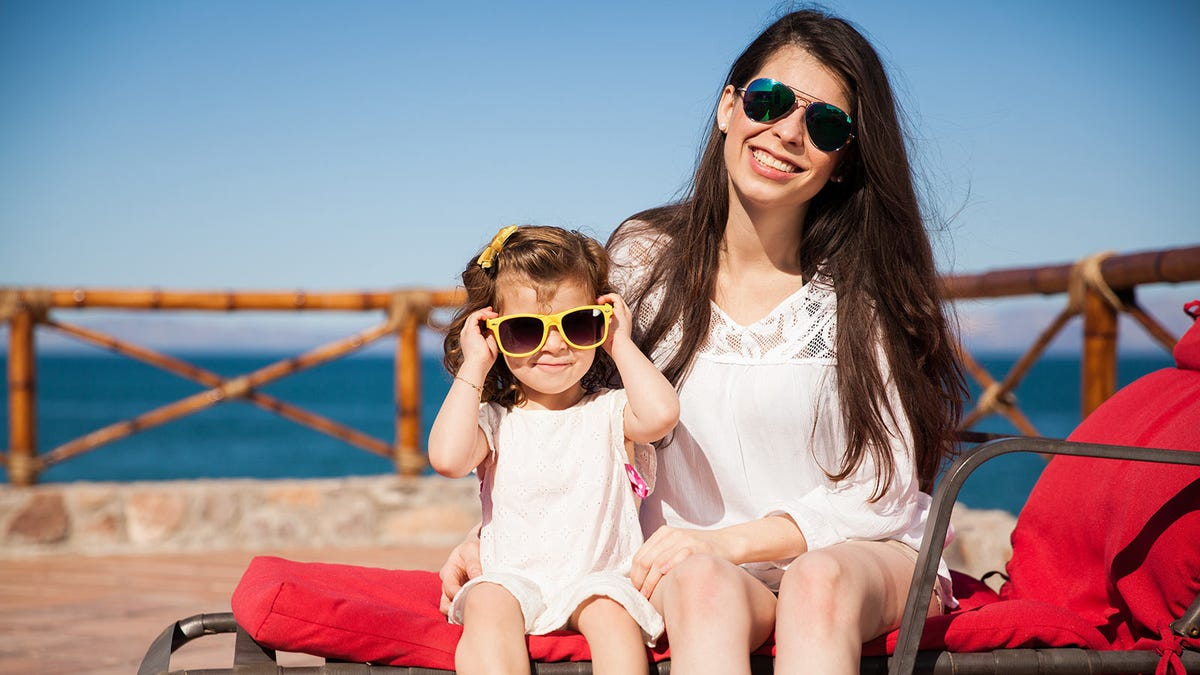 Mother and daughter sitting on a lounge chair and wearing sunglasses.