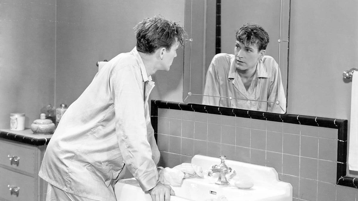 A 1940s era photo of a man wearing pajamas looking in a bathroom mirror.