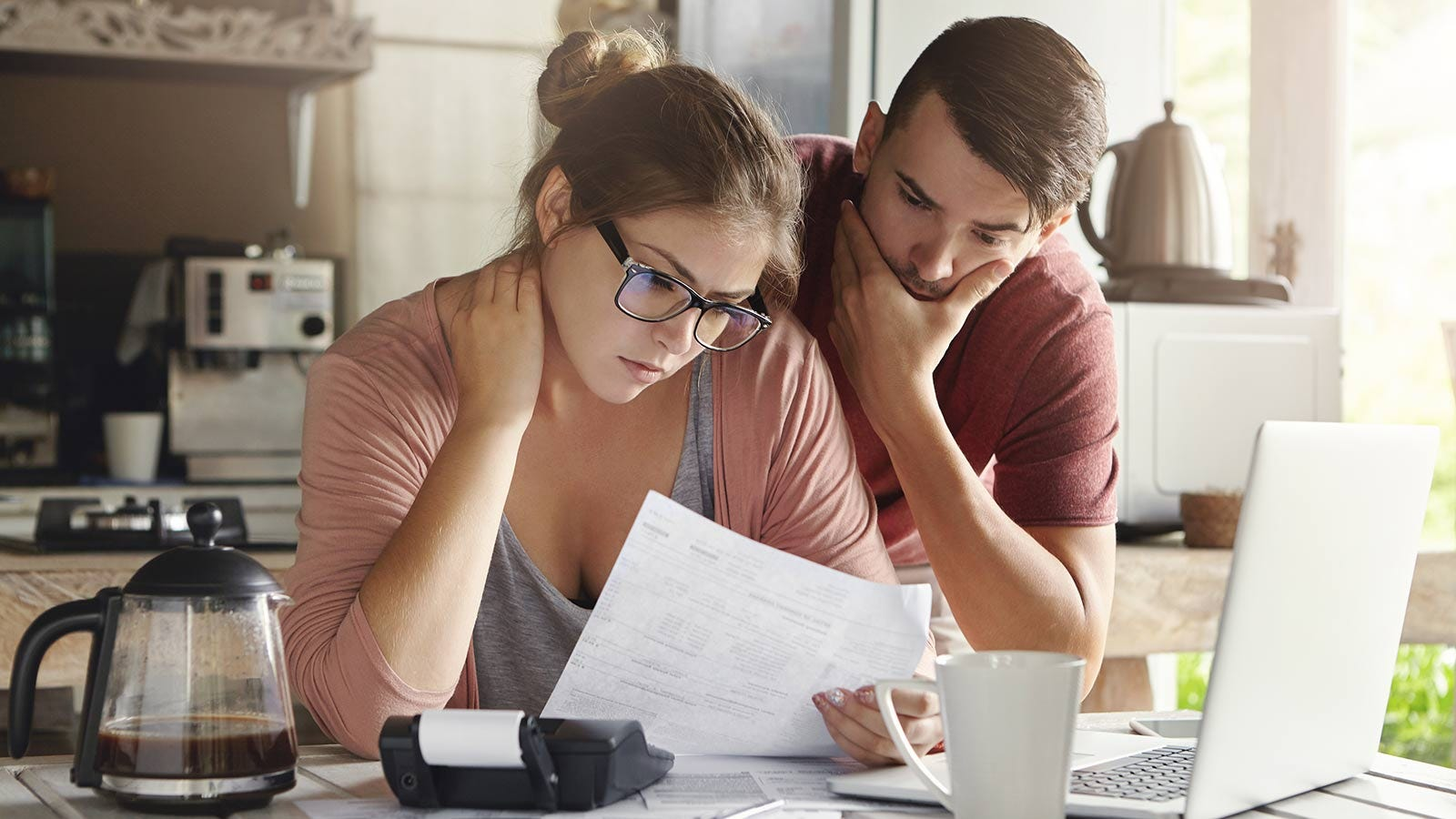 A man and woman looking at their bills with a calculator and laptop nearby.