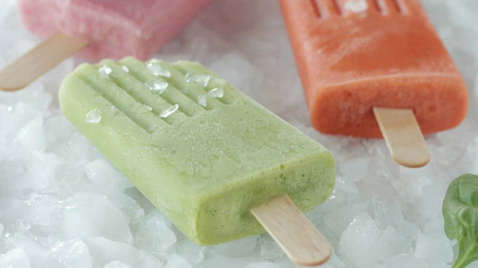Three homemade Popsicles resting on a bed of ice.