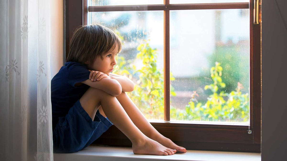 A boy sitting on a windowsill, sad because he can't play with his friends.