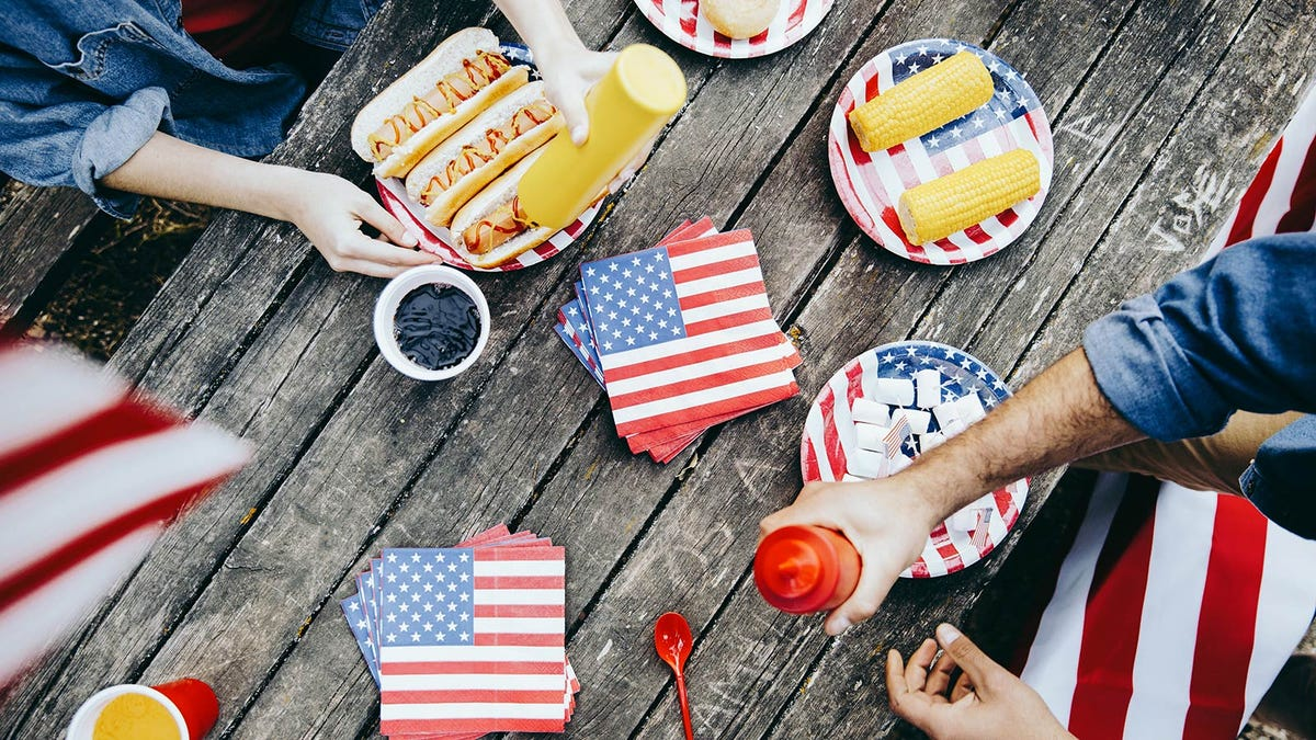 People putting ketchup and mustard on hot dogs and using American flag plates and napkins.