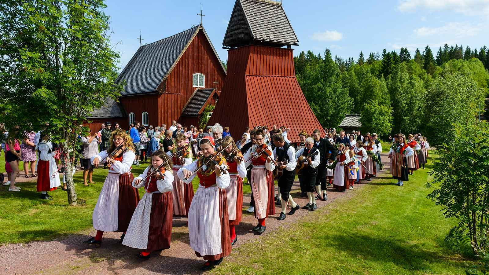 People in Sweden celebrating the Midsummer with music and traditional costumes.