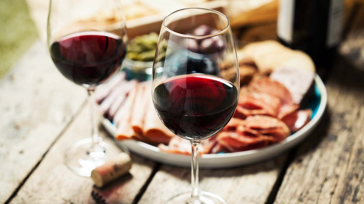 Two glasses of red wine next to a cheese board.
