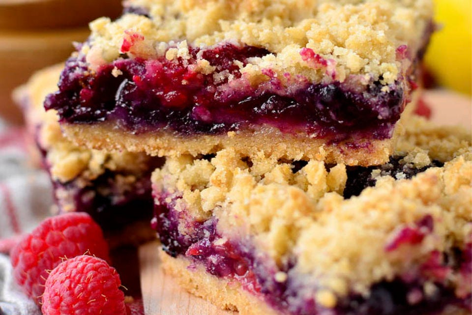 Three berry crumb bars piled on top of one another, with two raspberries on the side.