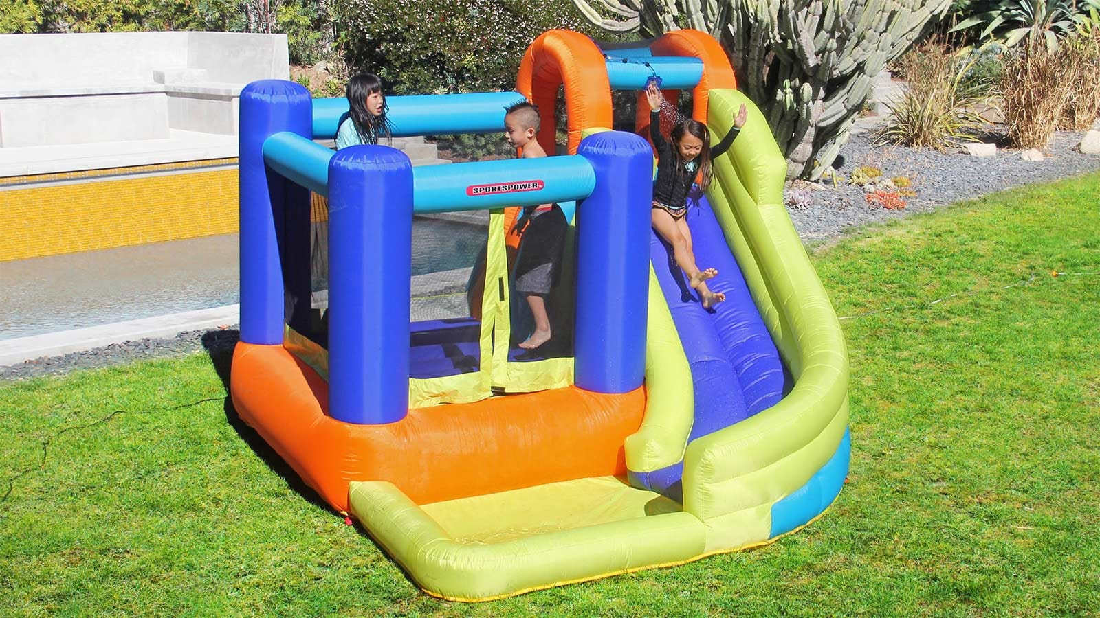 Kids playing outside on colorful bounce house with slide.