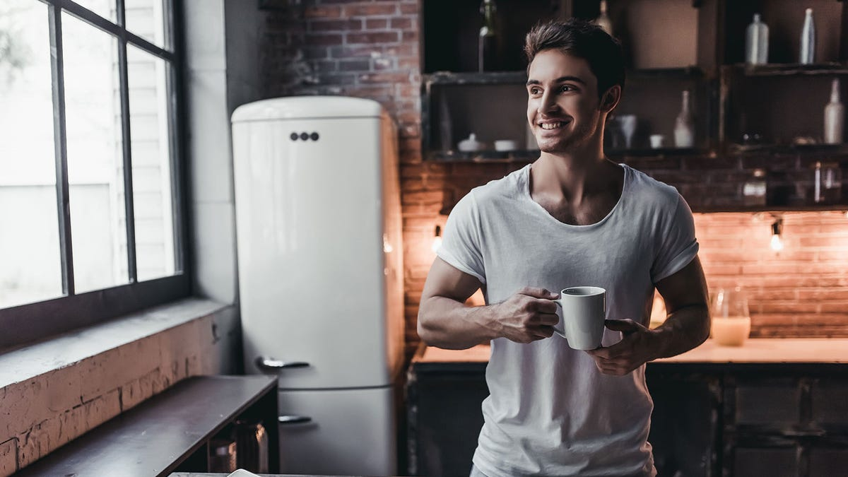 A man holding a mug of coffee in a kitchen.