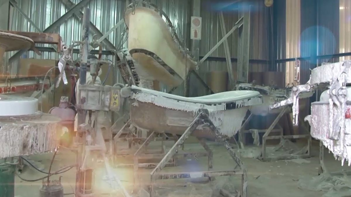 The inside of a bathtub factory showing a bathtub in the process of being coated with reinforcing fibers.