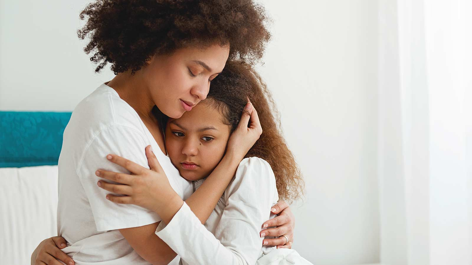 A mom hugging her daughter while listening to her concerns.