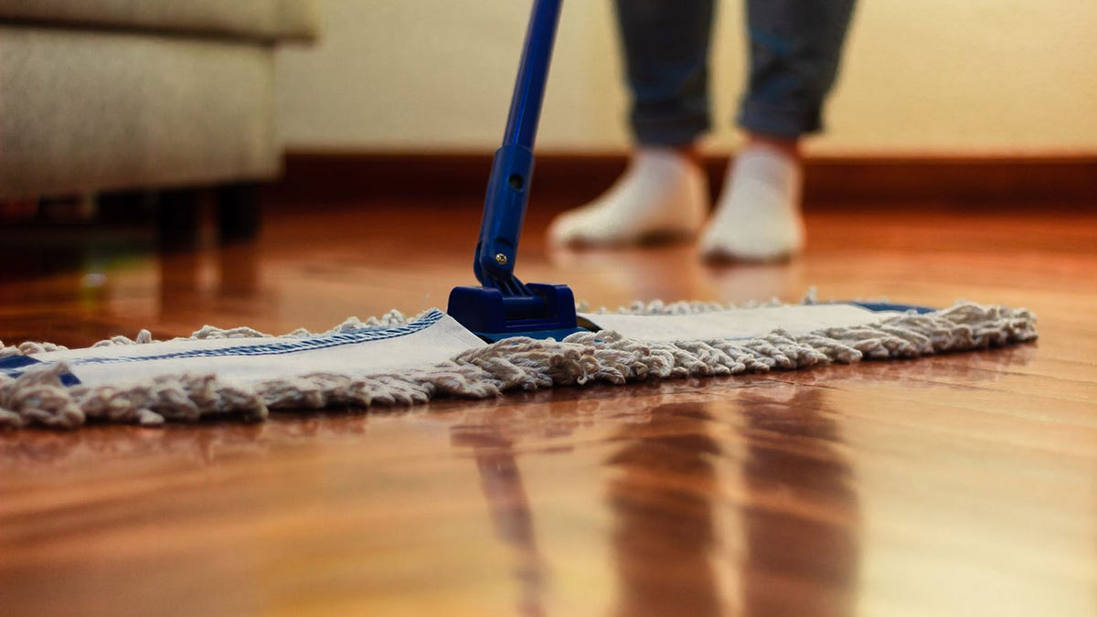 A person dust mopping hardwood floors with a wide paddle-style mop.