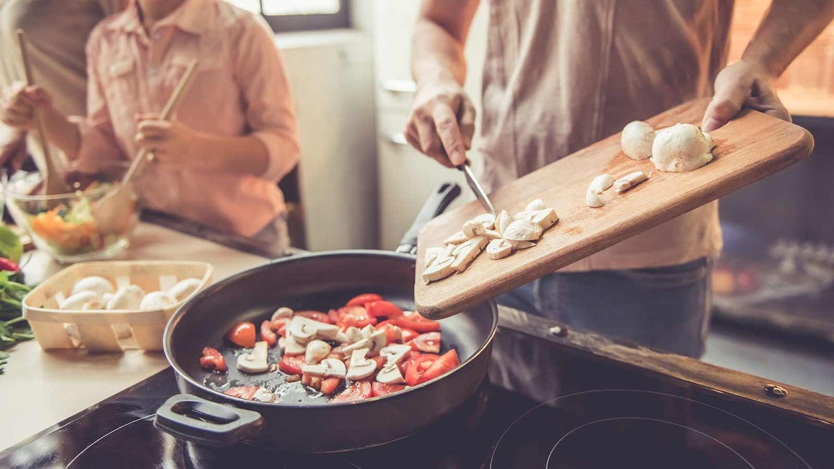 A family cooking at home, dumping ingredients from a cutting board into a skillet.