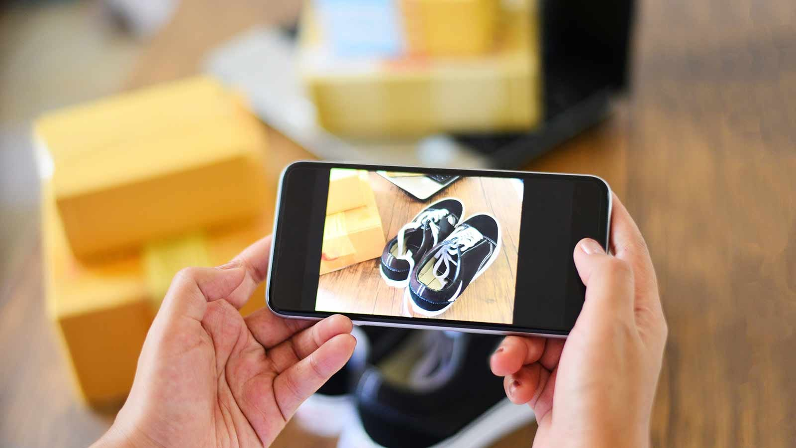 Person photographing a pair of sneakers with their cellphone.