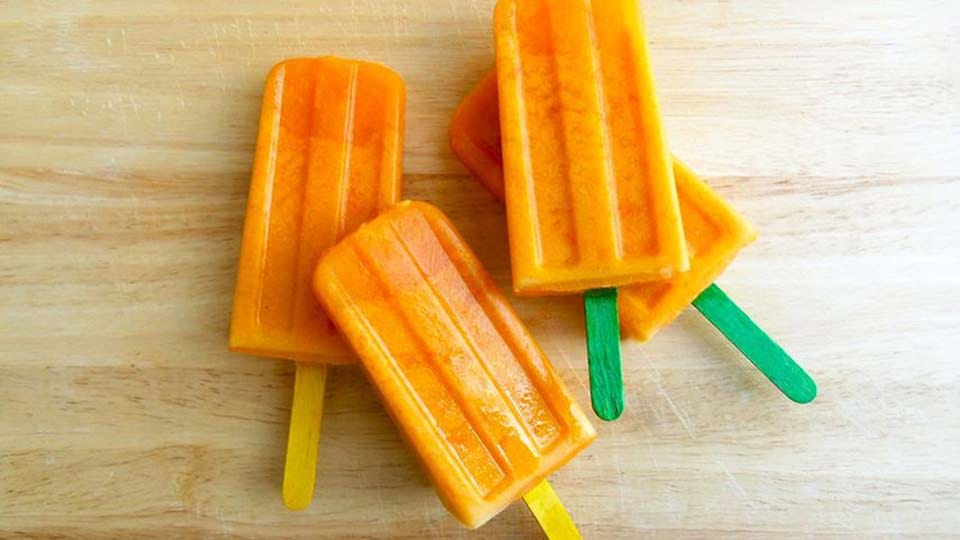 Four coconut carrot ice pops on a wooden cutting board.