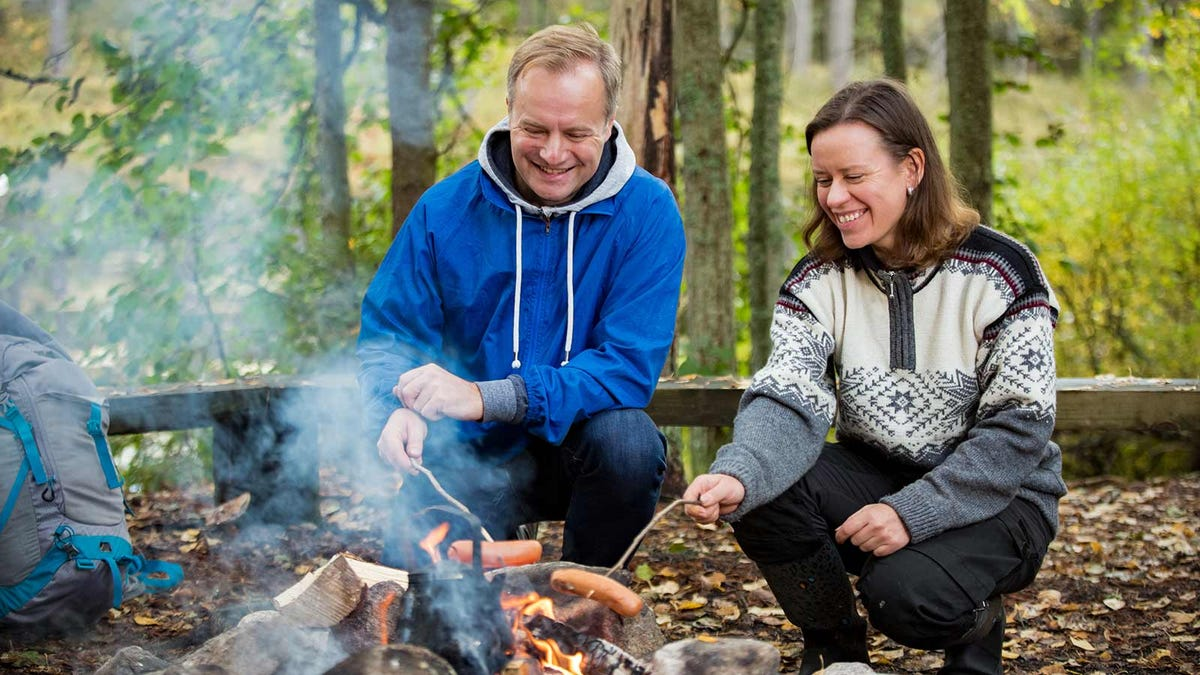 A man and woman roasting hot dogs over a campfire in the woods.
