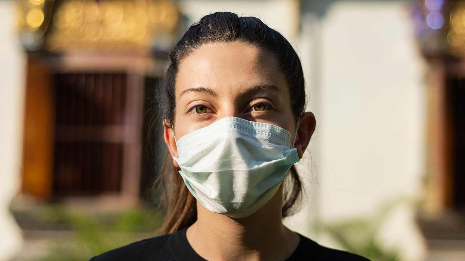 A woman wearing a disposable face mask.