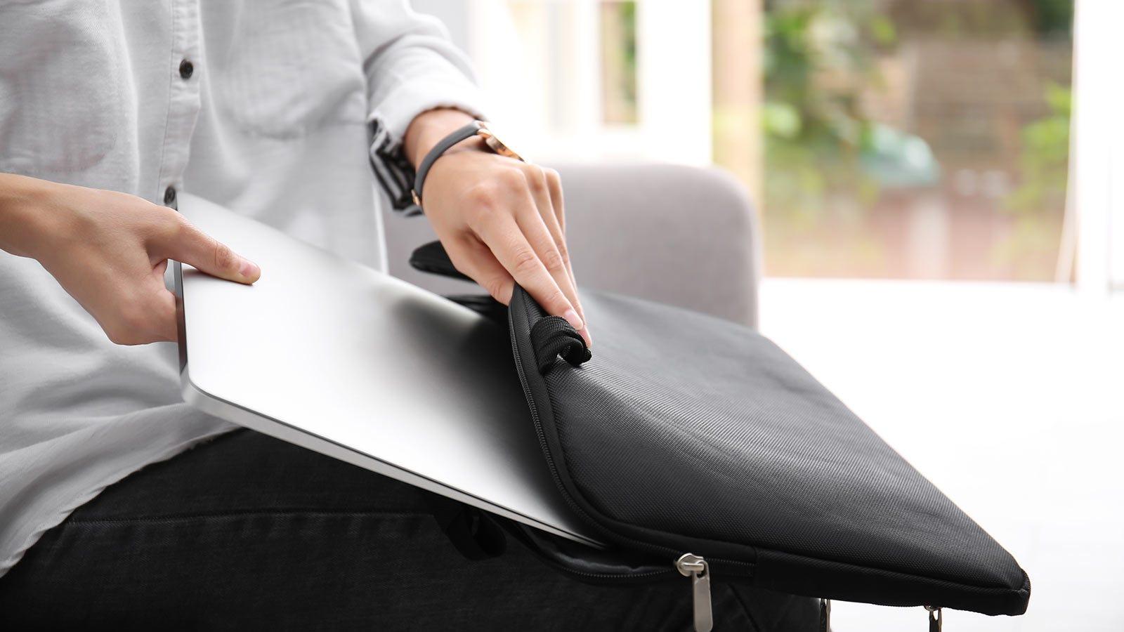 A woman sliding a laptop into a laptop sleeve.