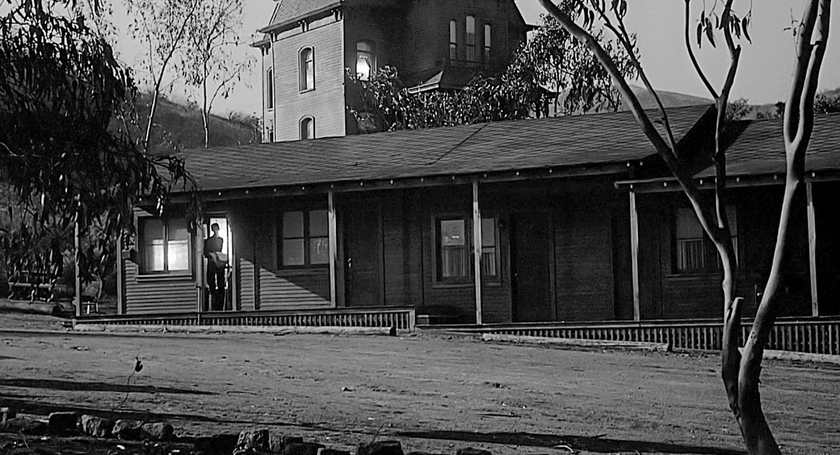 Still from the movie Psycho showing Norma Bates standing in doorway of a motel room.