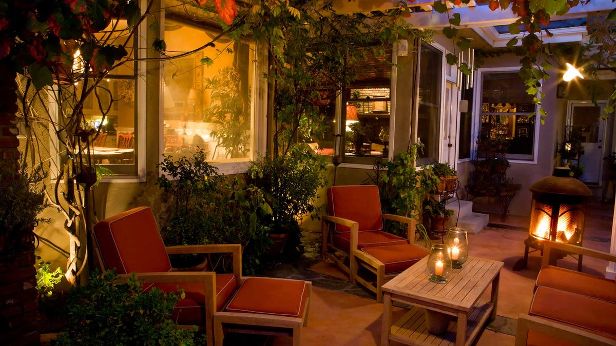 A cozy outdoor patio with seating, plants, and subtle lighting.