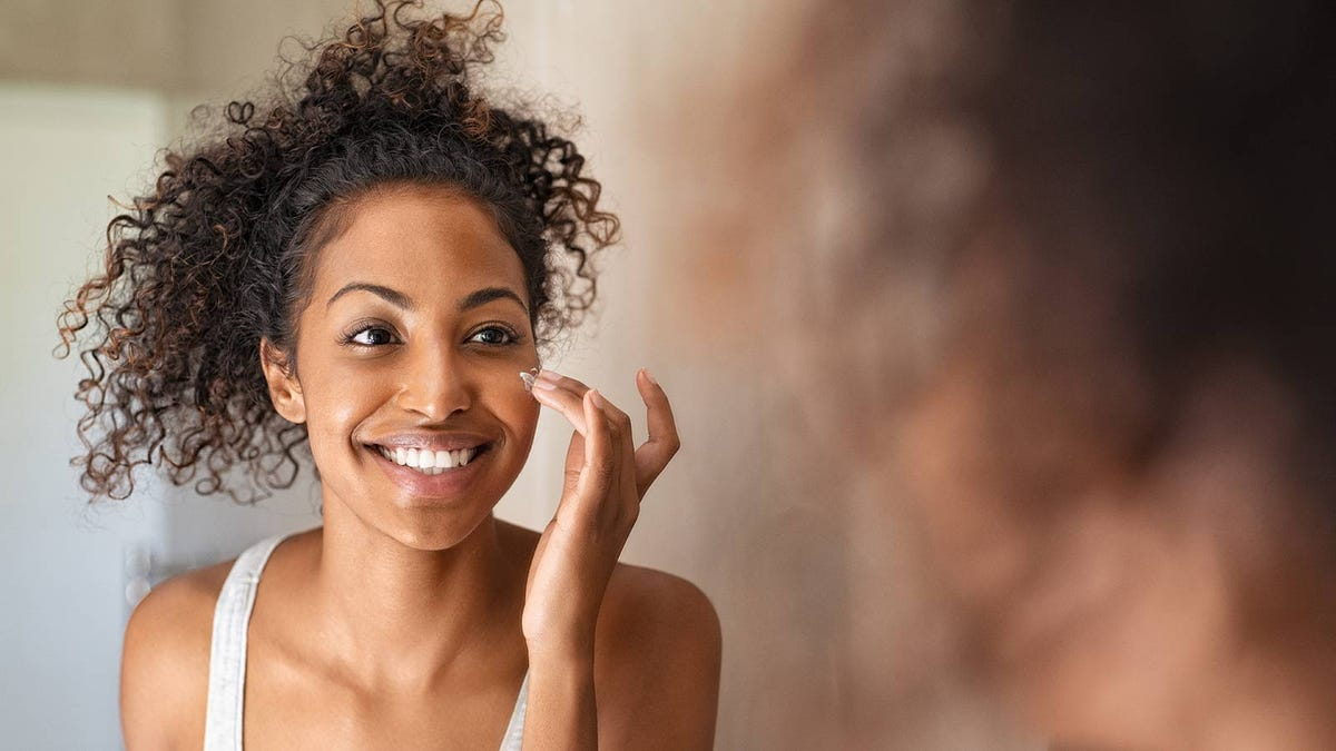 A young woman looking in the mirror applying a face cream.