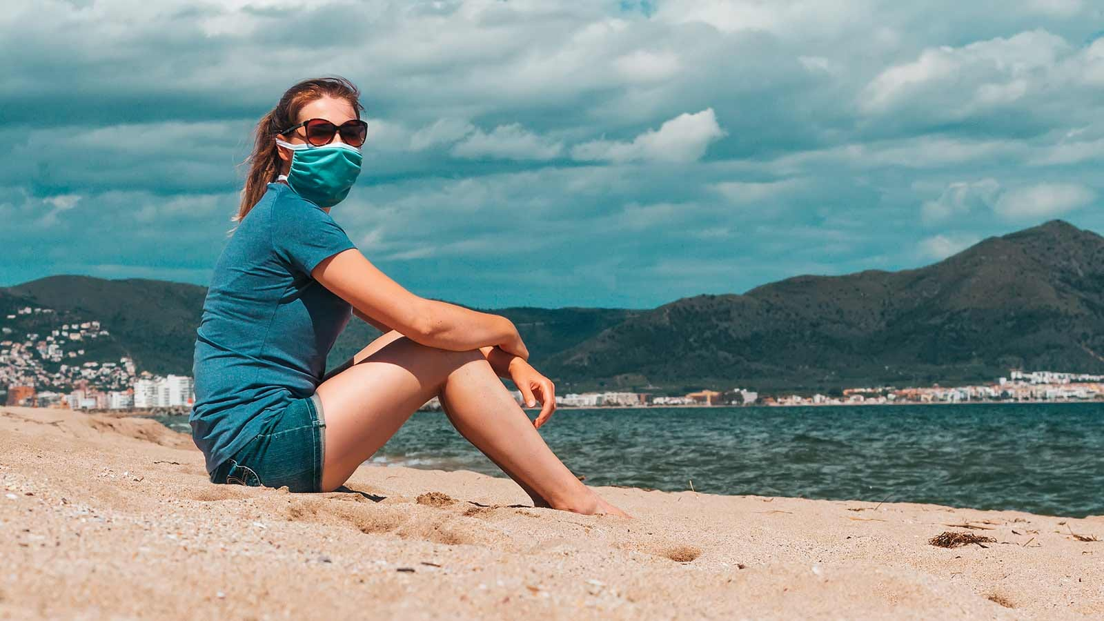A woman sitting on the beach wearing a cloth face mask.